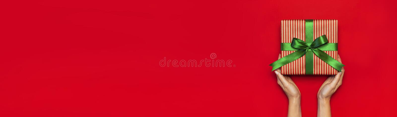 Gåvaasken med det gröna bandet i kvinnliga händer på röd lägenhet för bästa sikt för bakgrund lägger Semestra asken för det nya å arkivbilder