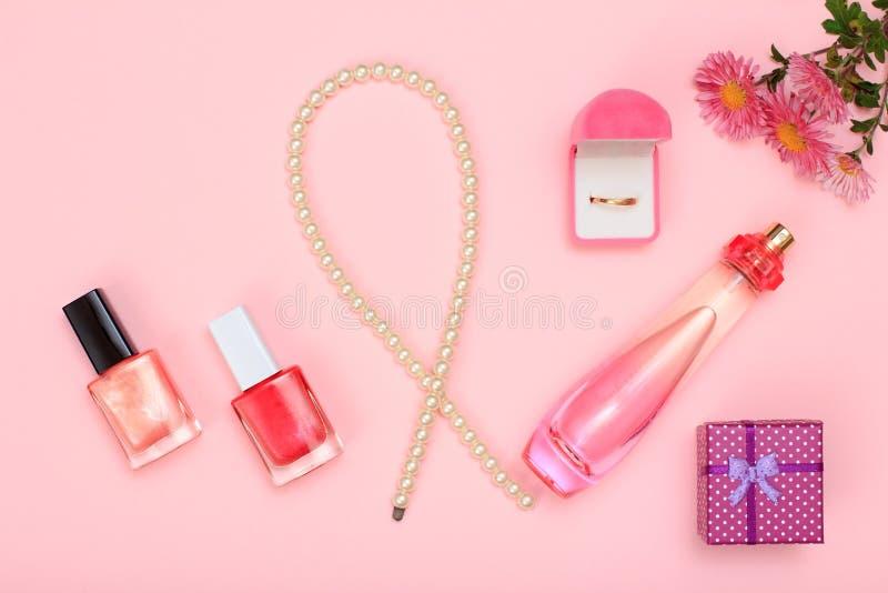 Gåvaasken, pärlor, flaska av doft, spikar polermedel och den guld- cirkeln i ask på en rosa bakgrund Kvinnaskönhetsmedel och till royaltyfria bilder