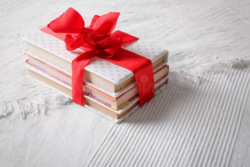 Gåvaböcker som slås in och förbindas beautifully med ett rött band bo arkivbild