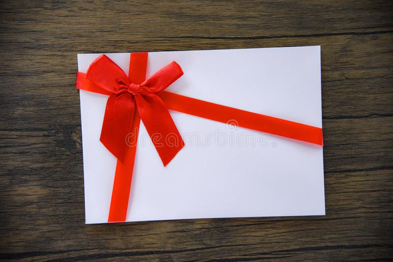 Gåvakort på träbakgrund/det rosa vita gåvakortet som dekoreras med den röda bandpilbågen fotografering för bildbyråer