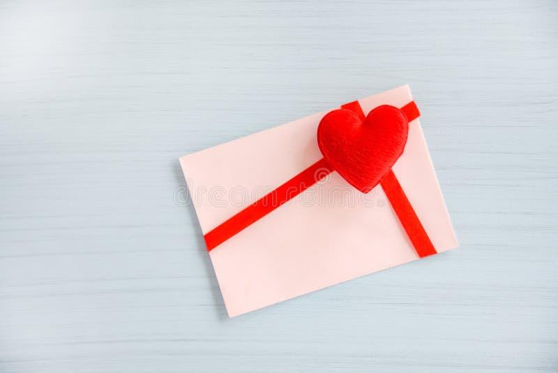 Gåvakort som dekoreras med den röda bandpilbågen och hjärta på vit träbakgrund fotografering för bildbyråer