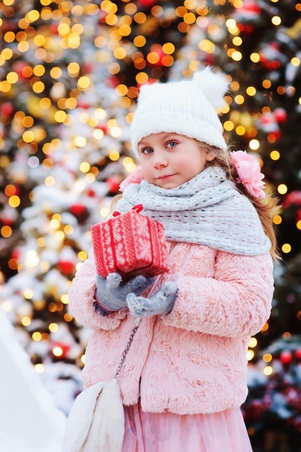 gåvan för jul för den lyckliga barnflickan som dekorerade den hållande var utomhus- på gå i snöig vinterstad, för nytt år royaltyfria bilder