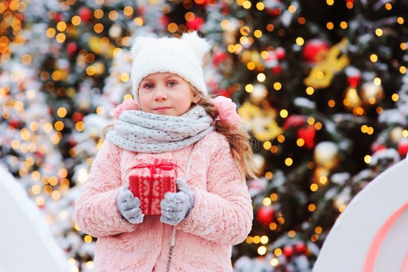 Gåvan för jul för den lyckliga barnflickan som semestrar den hållande är utomhus- på gå i den snöig vinterstaden som dekoreras fö fotografering för bildbyråer