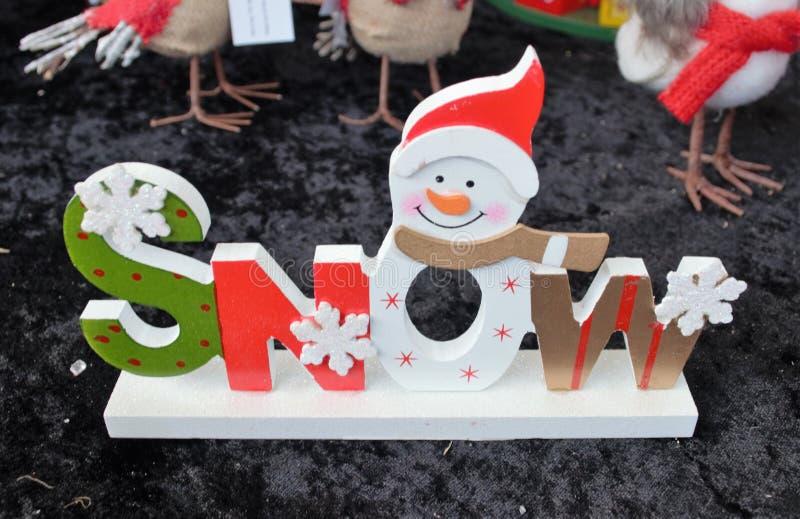 Gåvan för juldekorerade den träsnösnögubben med snöflingor arkivfoto
