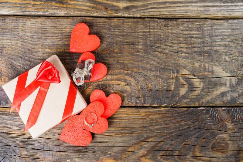Gåvan packas i Kraft papper, och bundet med ett rött band steg Gåvan som omges av dekorativa hjärtor en, är en vigselring med arkivbild