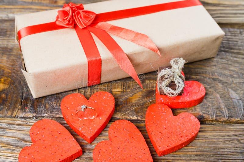 Gåvan packas i Kraft papper, och bundet med ett rött band steg Gåvan som omges av dekorativa hjärtor en, är en vigselring med royaltyfria bilder