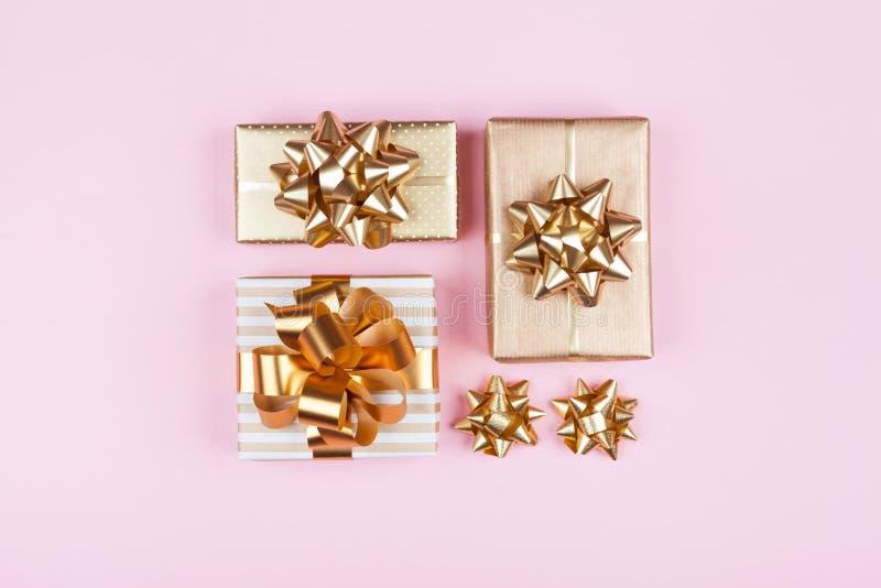 Gåvor eller framlägger askar med guld- pilbågar på bästa sikt för rosa pastellfärgad bakgrund Lägenhet som är lekmanna- för födel arkivbild