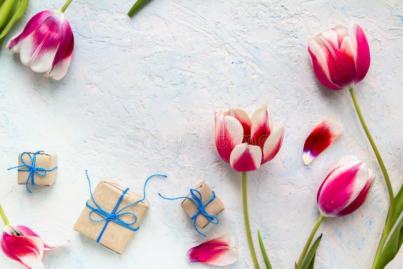 Gåvor i hantverkpacke med blommor royaltyfria bilder