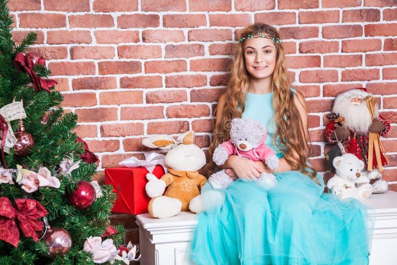 Gåvor och julbegrepp Den tonårs- långa haired blondinen sitter på en vit nightstand nära julträd royaltyfri foto