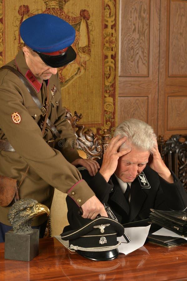 Général mûr militaire menacé par soldat photos libres de droits