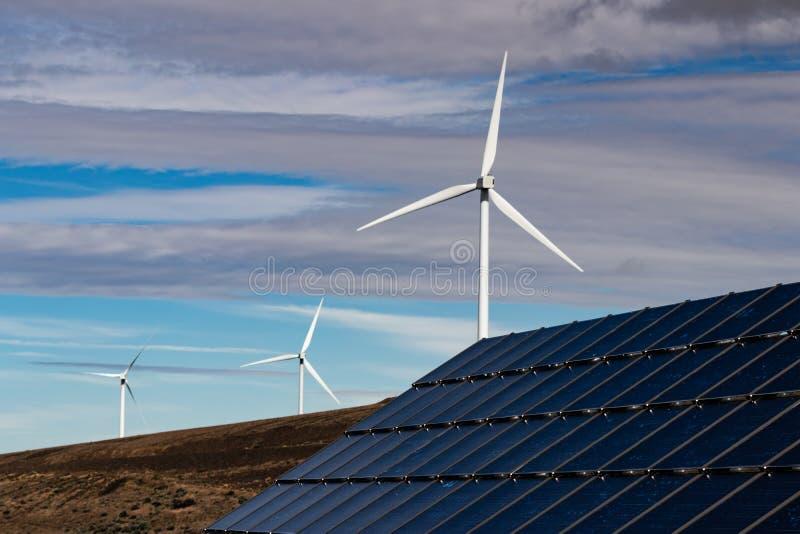 Générateurs viables verts de l'électricité de turbine de puissance de moulin à vent d'énergie et piles solaires avec les nuages e image libre de droits