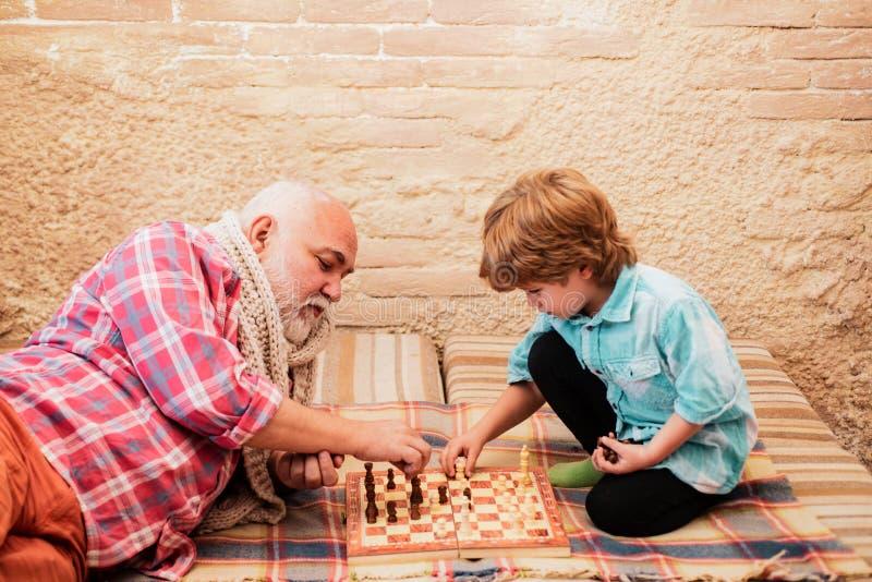 Générations Matelot de contrôle Homme de haut niveau enseignant à son petit-fils de jouer aux échecs Chessman Pièce d'échecs images stock