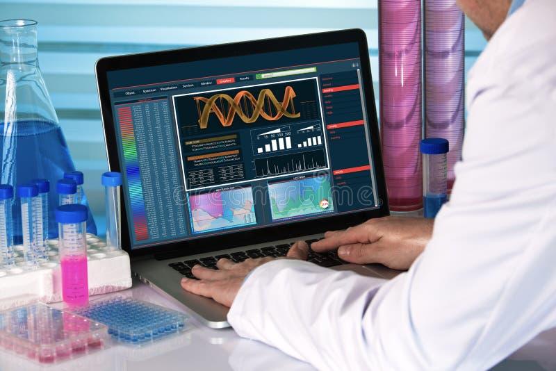 Généticien de recherches employant le laboratoire de biotechnologie d'ordinateur image stock