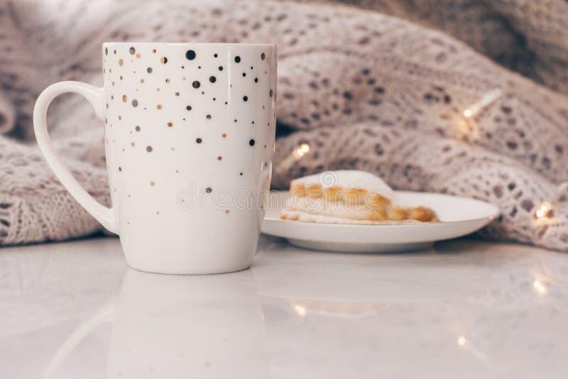 Géneros de punto acogedores y una taza de café con una torta en el alféizar de mármol blanco contra el fondo blanco de la ventana imagen de archivo libre de regalías