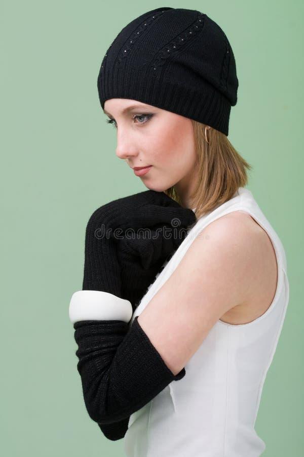 Géneros de punto. mujer joven que desgasta un casquillo del invierno foto de archivo