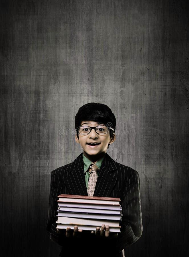 Génie Little Boy tenant des livres portant des lunettes, souriant près de C photos stock