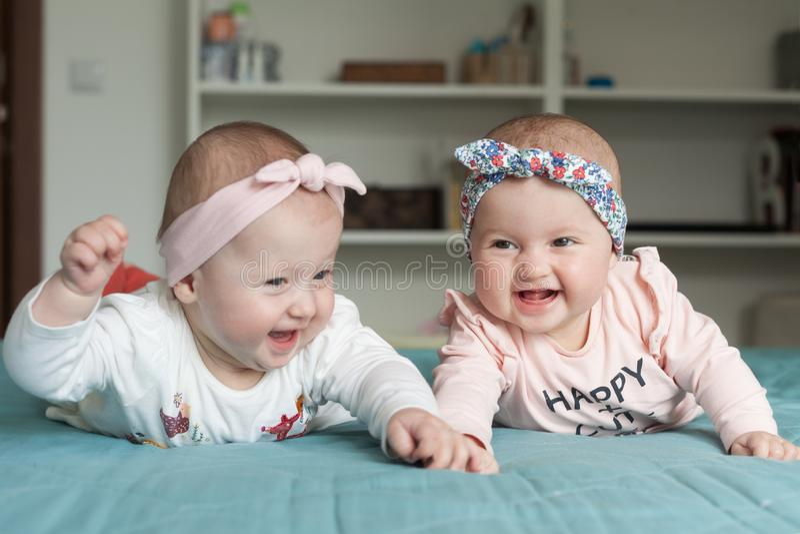 Gêmeos adoráveis do bebê que têm o divertimento na cama em casa Crianças bonitos com fitas dos hairbands, sorrindo, rindo Conceit fotos de stock