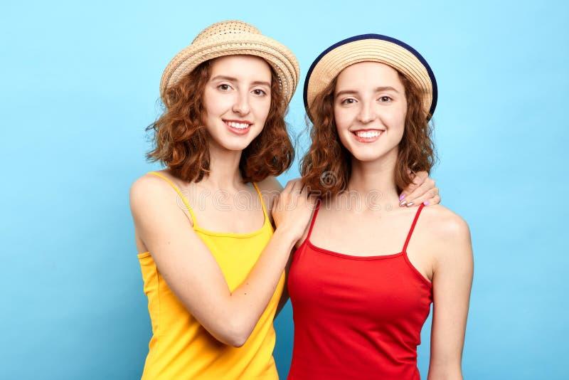 Gêmeos alegres positivos em chapéus à moda e em partes superiores vermelhas e amarelas foto de stock