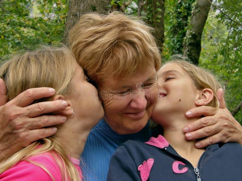 Gêmeos, beijo da irmã uma avó fotografia de stock royalty free