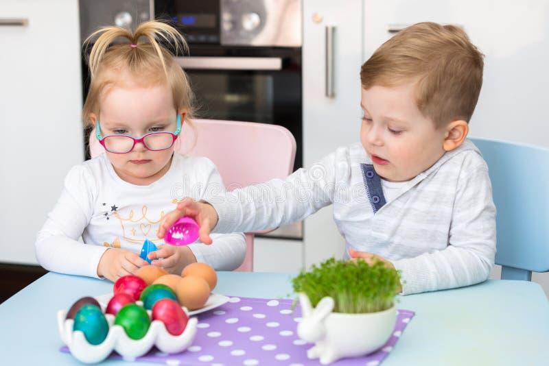Gêmeos do menino e da menina que pintam ovos para a Páscoa fotos de stock