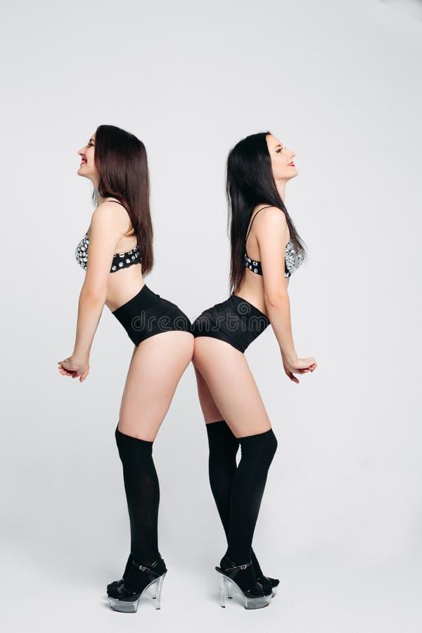 Gêmeos 'sexy' e bonitos na roupa interior que inclina-se e o levantamento imagens de stock