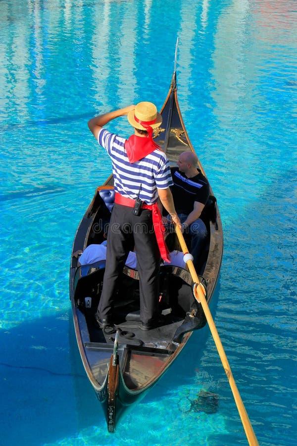Góndola con los turistas en un canal, un hotel turístico veneciano y un casi fotografía de archivo