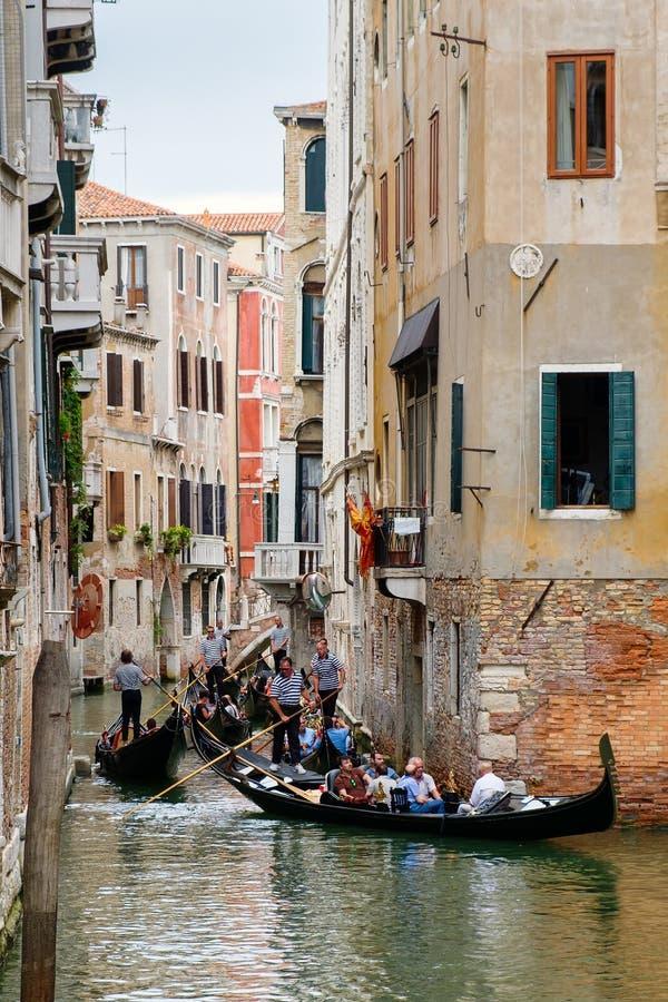 Góndolas en un canal estrecho rodeado por los edificios viejos en Venecia foto de archivo