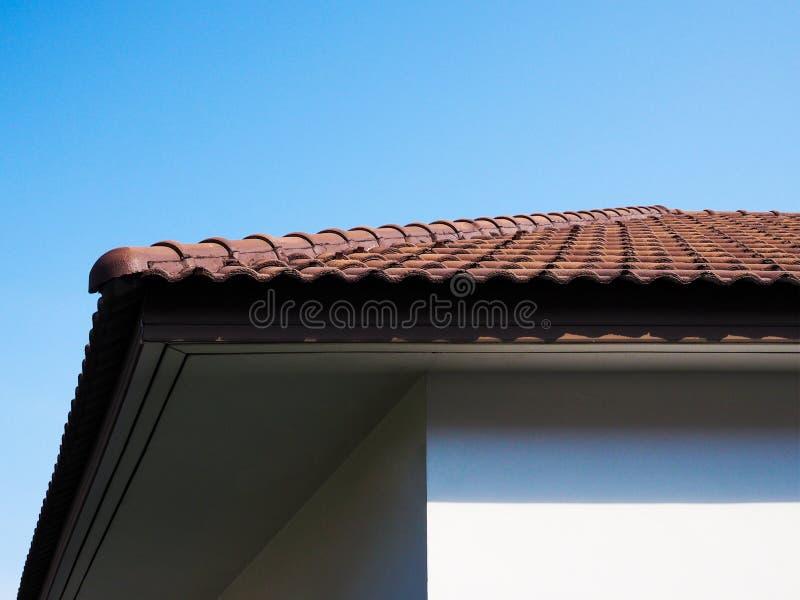 Góra domu z dachowymi dachówkami terakotą i niebieskim tłem nieba obraz stock