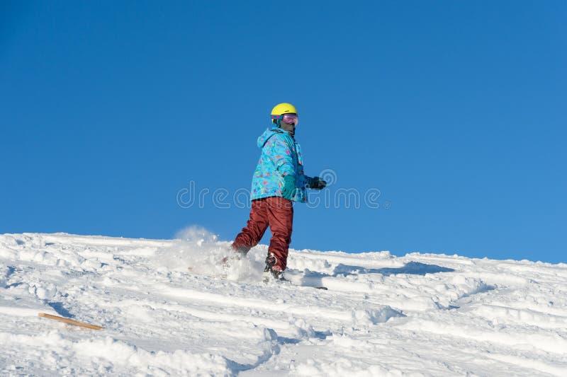 GÓRA ELBRUS ROSJA, LISTOPAD, - 30, 2017: Snowboard dziewczyna jest ubranym słońce maskę i szalika jedzie w dół wysokogórskiego fotografia stock