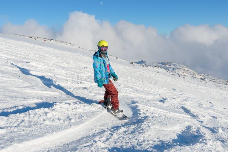 GÓRA ELBRUS ROSJA, LISTOPAD, - 30, 2017: Snowboard dziewczyna jest ubranym słońce maskę i szalika jedzie w dół wysokogórskiego zdjęcia stock