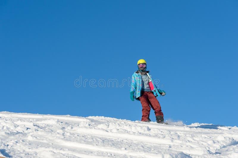 GÓRA ELBRUS ROSJA, LISTOPAD, - 30, 2017: Snowboard dziewczyna jest ubranym słońce maskę i szalika jedzie w dół wysokogórskiego zdjęcie royalty free