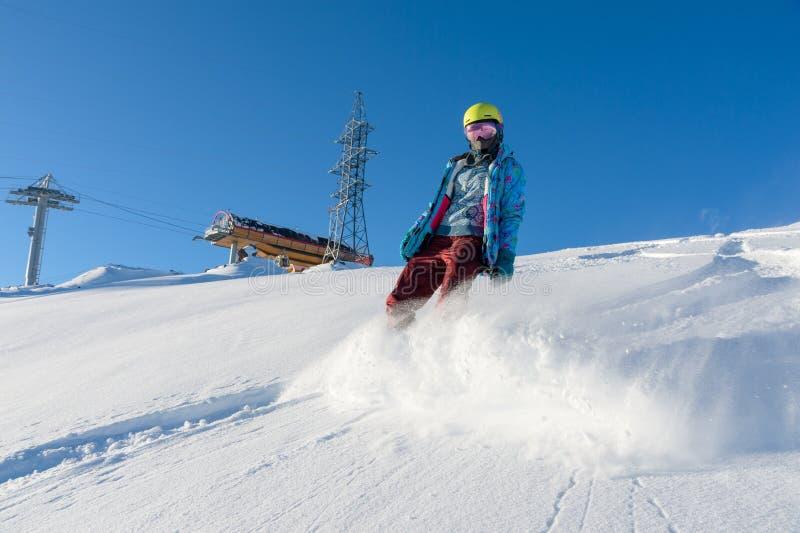 GÓRA ELBRUS ROSJA, LISTOPAD, - 30, 2017: Snowboard dziewczyna jest ubranym słońce maskę i szalika jedzie w dół wysokogórskiego obrazy royalty free