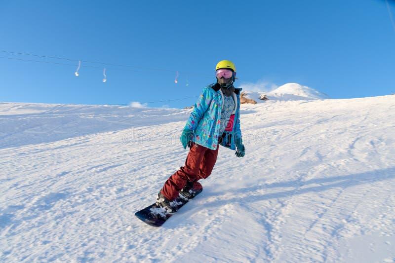 GÓRA ELBRUS ROSJA, LISTOPAD, - 30, 2017: Snowboard dziewczyna jest ubranym słońce maskę i szalika jedzie w dół wysokogórskiego fotografia royalty free