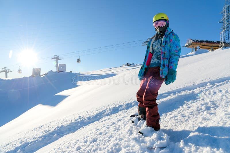GÓRA ELBRUS ROSJA, LISTOPAD, - 30, 2017: Snowboard dziewczyna jest ubranym słońce maskę i szalika jest statywowa na skłonie _ zdjęcia royalty free