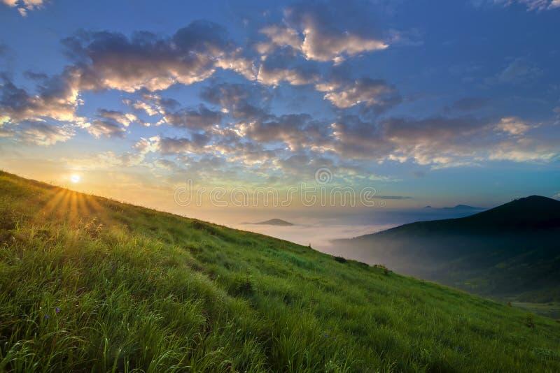 Góra krajobraz w ładnej pogodzie przy wschodem słońca Zielony trawiasty stee obrazy stock