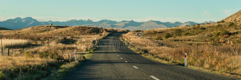 Góra krajobraz z drogą i niebieskim niebem, Otago, Nowa Zelandia fotografia royalty free