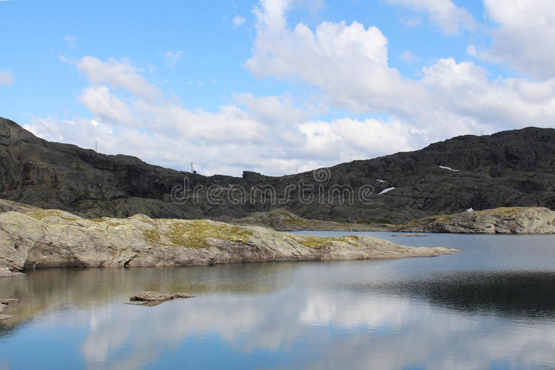 Góra niebieskie niebo z niektóre i jezioro chmurniejemy fotografia royalty free
