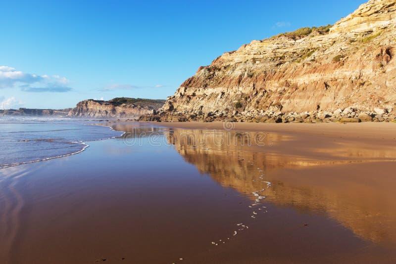 Góra odbijał w gładkiej wodzie plażowy Areia Branca Lourinha, Portugalia, zdjęcia stock
