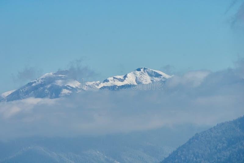 góra panoramiczny widok W pierwszoplanowych chmurach w środkowej śnieżystej zimie lasowy Lago-Naki magistrala Kaukaska obraz stock