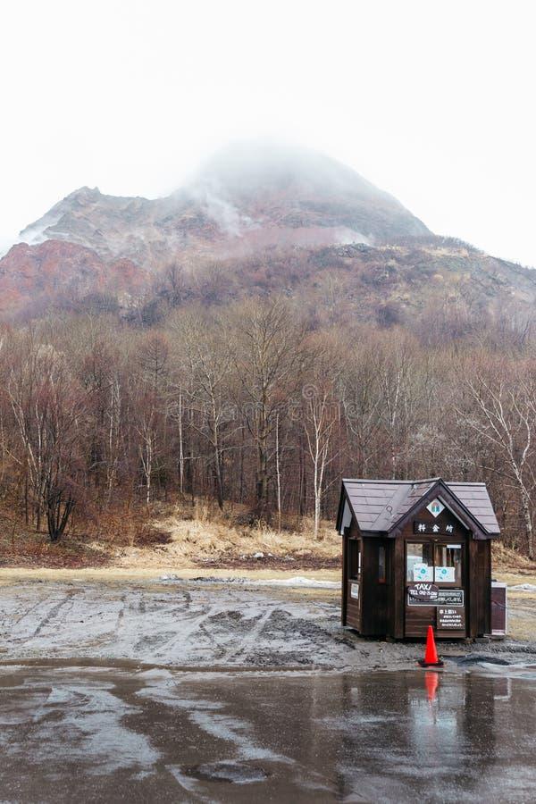 Góra z śniegiem i mgła na wierzchołku, drzewach i strażowym domu below przy carpark Noboribetsu niedźwiedzia park w hokkaidu, Jap zdjęcie royalty free