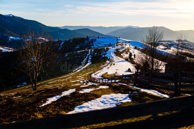 Górkowaty teren zakrywający z roztapiającym śniegiem niebieska spowodowana pola pełne się chmura dzień zielonych roślin krajobraz zdjęcia stock
