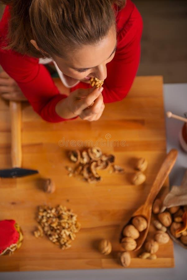 Górna widok gospodyni domowa bierze kąsek orzech włoski podczas gdy gotujący obrazy stock