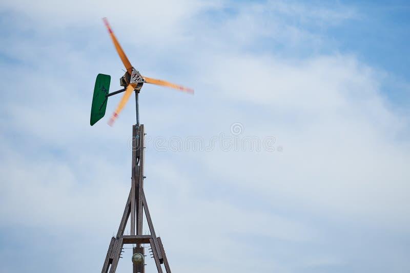 Górny koniec jaźni budowy silnik wiatrowy robić z drewna podczas gdy wytwarzający energię przed chmurzącym niebem Ostrza zamazują zdjęcia stock