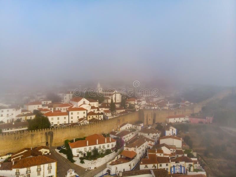 Górny widok czerwoni dachy mały miasto blisko rzeki wśród wzgórzy przeciw niebieskiemu niebu i bielowi chmurnieje zdjęcia stock