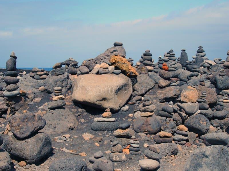 Góruje brogujący kamienie w różnych colours w wielkim przygotowania na czarnej piasek plaży z niebieskim niebem i otoczaki zdjęcia stock