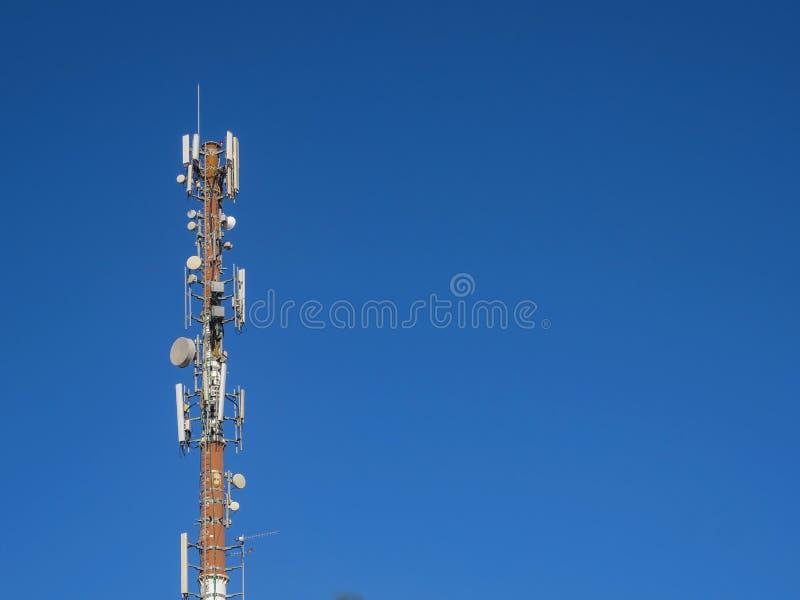Góruje z antenami komórkowa komunikacja przeciw tłu niebieskie niebo zdjęcia royalty free