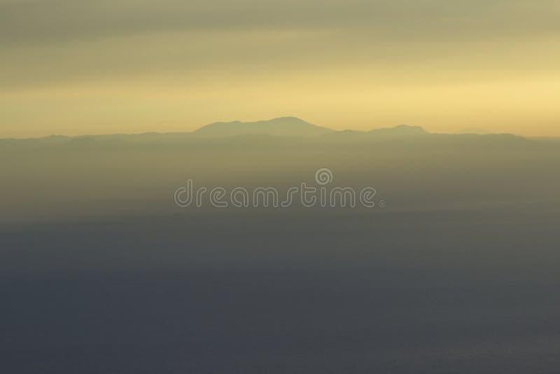 Góry i morze, zmierzch, niebo w pastelowych kolorach, lekka mgiełka, plama fotografia royalty free