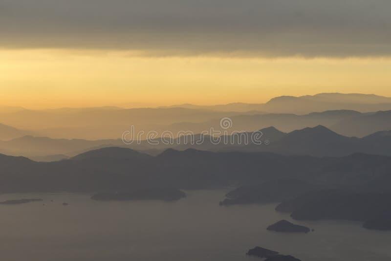 Góry i morze, zmierzch, niebo w pastelowych kolorach, lekka mgiełka, plama obraz stock