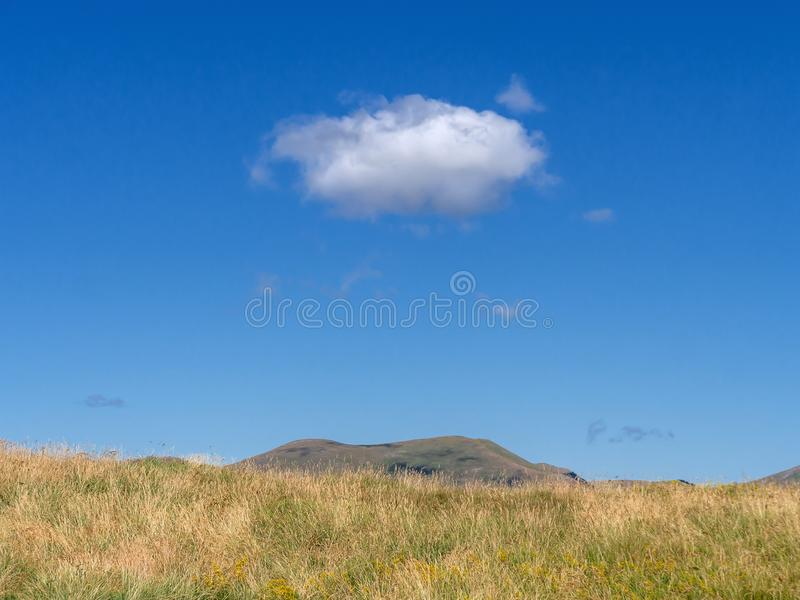 Góry trawy odgórna łąka sk z pojedynczą chmurą nad i jaskrawy błękitny gorący lato T?o obraz royalty free