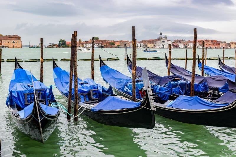 Gôndola vazias entradas entre os polos de amarração de madeira cobertos no encerado na estação chuvosa de novembro em Veneza, Itá imagens de stock